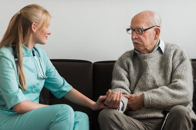 Krankenschwester tröstet alten mann in einem pflegeheim