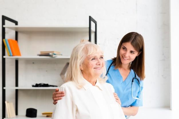 Krankenschwester und alte frau, die auf dem fenster schauen