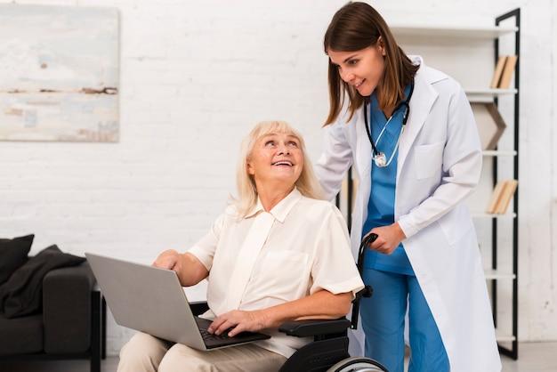 Krankenschwester und alte frau, die einen laptop überprüfen