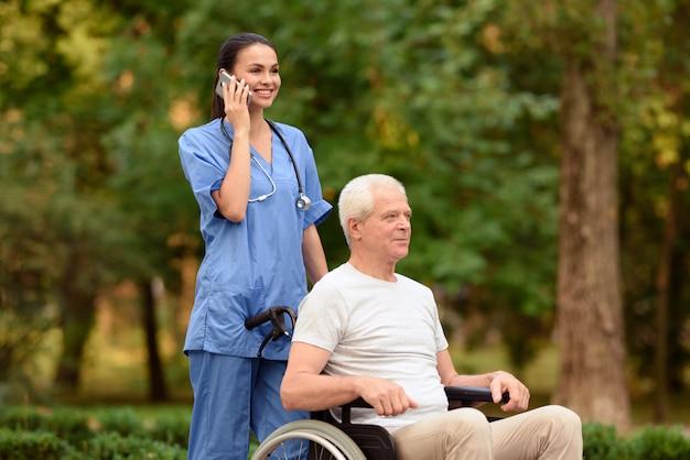 Krankenschwester und alter mann, die in einem rollstuhl im park sitzen.