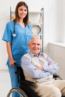 Krankenschwester und alter mann posiert für die kamera