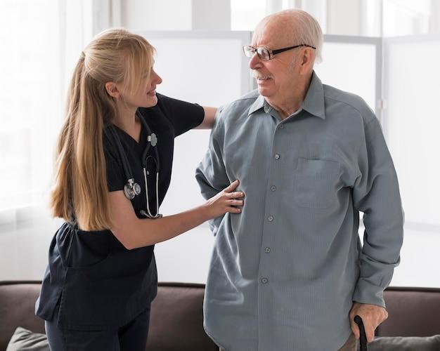 Krankenschwester und alter mann zusammen in einem pflegeheim