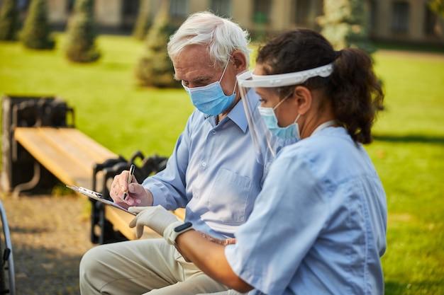 Krankenschwester und alter patient auf bank in der nähe des altenheims