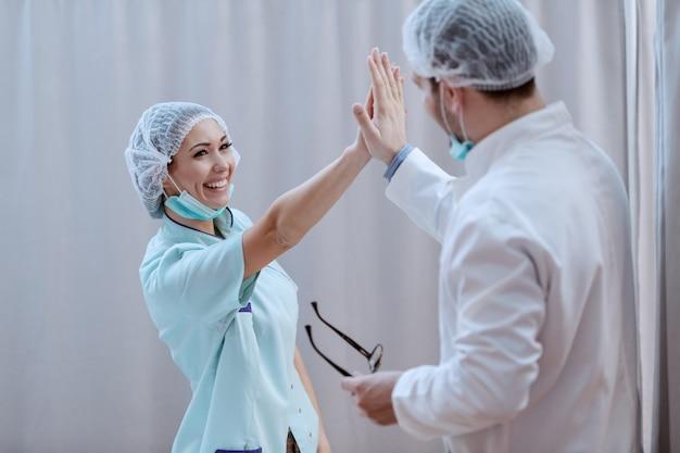 Krankenschwester und arzt geben high five.