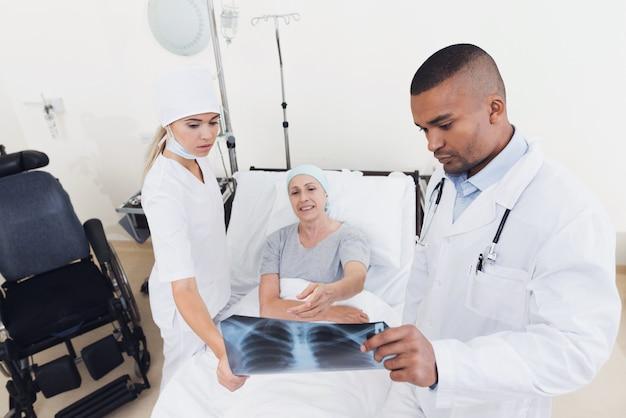 Krankenschwester und arzt stehen neben patienten mit krebs