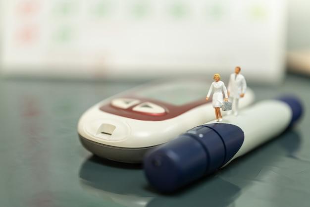 Krankenschwester und doktor miniaturfigur mit handtasche, die auf lanzette mit glukosemessgerät und kalender läuft.