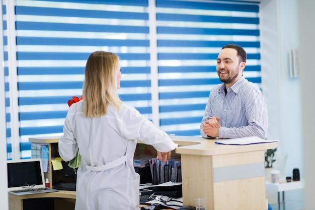 Krankenschwester und patient unterhalten sich an der rezeption im krankenhaus