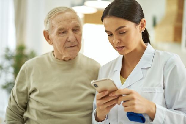 Krankenschwester und senior, die auf den bildschirm des handys schauen