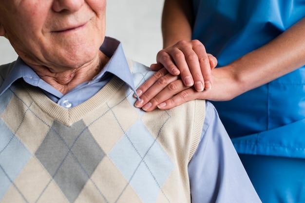 Krankenschwester, welche die schulternahaufnahme des alten mannes hält
