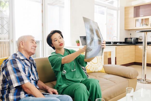 Krankenschwester zeigt dem älteren mann röntgenaufnahme der brust