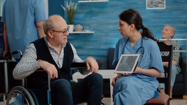 Krankenschwester zeigt einem behinderten alten mann osteopathie-röntgen auf tablet