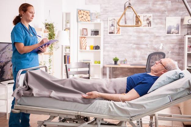 Krankenschwester zur kenntnisnahme der zwischenablage im pflegeheim im gespräch mit dem alten mann.