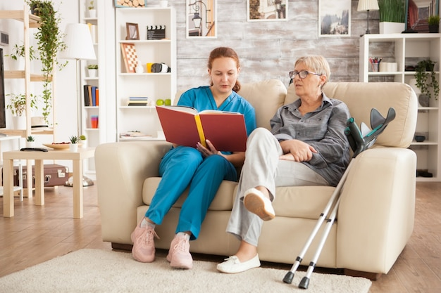 Krankenschwesterfrau, die ein buch über pflegeheim für kranke ältere frau liest.