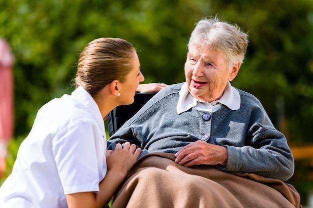 Krankenschwesterhändchenhalten mit älterer frau im rollstuhl