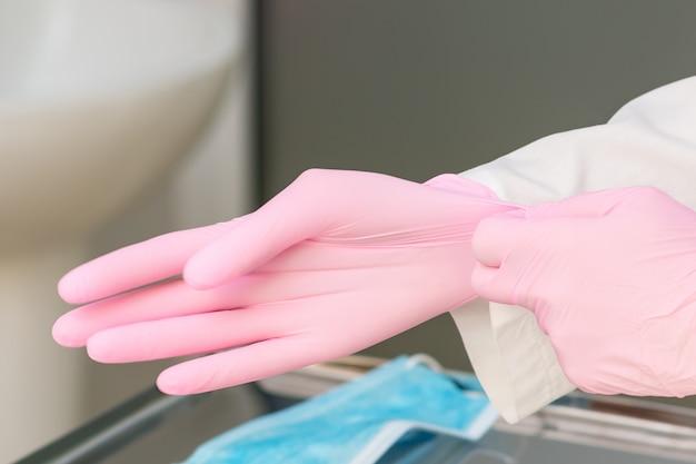 Krankenschwesterhände zieht rosa handschuhe im krankenhaus an.