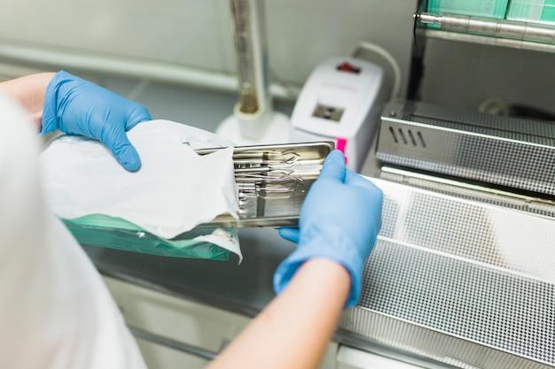 Krankenschwesterhand, die zahnmedizinisches instrument in der plastiktasche verpackt