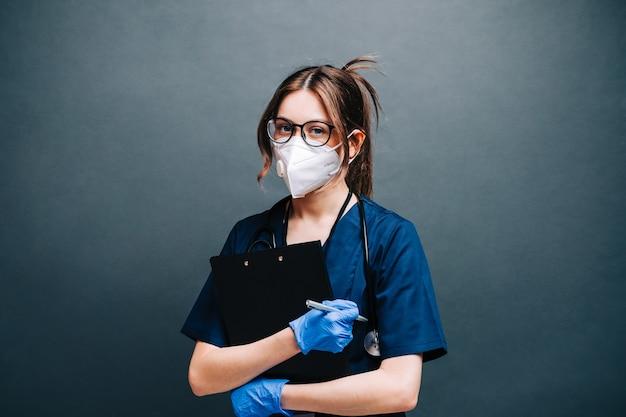 Krankenschwesterkrankenhausarbeiter der jungen frau in der medizinischen schutzmaske, die notizblock lokalisiert auf grauem hintergrund hält.