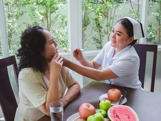 Krankenschwestern füttern ältere menschen mit äpfeln