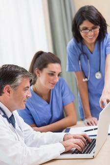 Krankenschwestern und doktor, die laptop betrachten