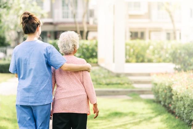 Krankenschwestersorgfaltunterstützung, die mit der älteren frau im freien geht