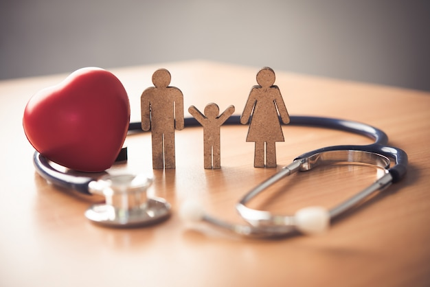 Krankenversicherung mit familie und stethoskop auf hölzernem schreibtisch