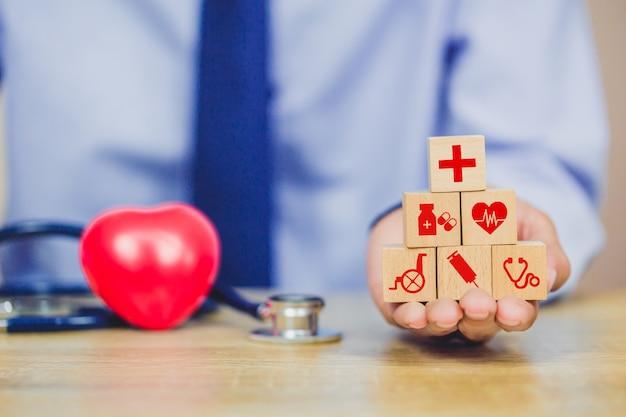 Krankenversicherungs-konzept, hand, die das stapeln des hölzernen blockes vereinbart