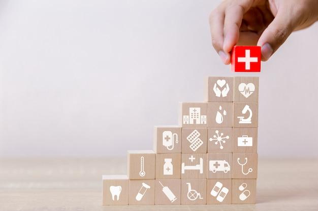 Krankenversicherungs-konzept, hand, die den hölzernen block stapelt mit dem ikonengesundheitswesen medizinisch, für gesundheit vereinbart