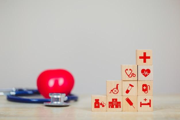 Krankenversicherungs-konzept, hand, die den hölzernen block stapelt mit dem ikonengesundheitswesen medizinisch vereinbart