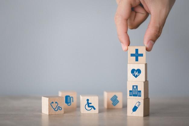 Krankenversicherungs-konzept, hand, die den hölzernen block stapelt mit dem ikonengesundheitswesen medizinisch vereinbart.
