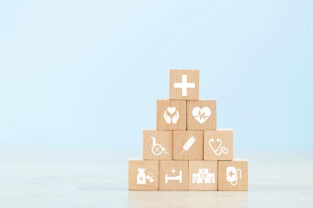 Krankenversicherungs-konzept, hölzernen block vereinbarend, der mit dem ikonengesundheitswesen stapelt, das medizinisch ist.