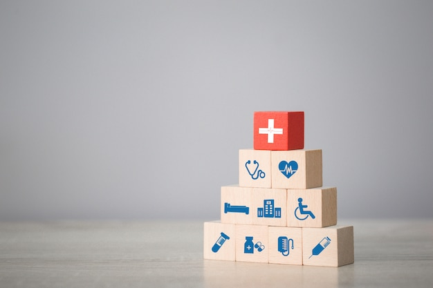 Krankenversicherungskonzept, das das stapeln von holzblöcken mit der medizinischen ikone des gesundheitswesens anordnet.