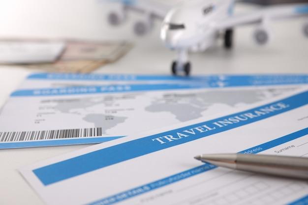 Krankenversicherungsvertrag für touristen mit stift und flugzeug auf dem tisch. medizinische behandlung im urlaubskonzept