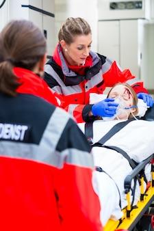 Krankenwagen, der verletzter frau auf bahre hilft