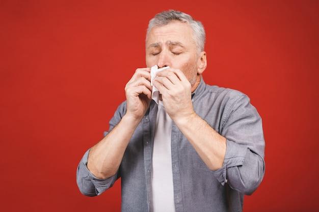 Kranker älterer mann, der seine nase mit taschentuch putzt. grippe haben, aller