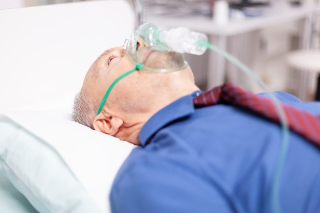 Kranker älterer mann mit covid19 infiziert, der in einer privatklinik durch eine sauerstoffmaske atmet