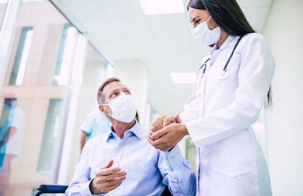 Kranker älterer mann mit schützender sicherheitsmaske im gesicht im rollstuhl und einem selbstbewussten arzt in der medizinischen maske während des transports auf dem krankenhaus.