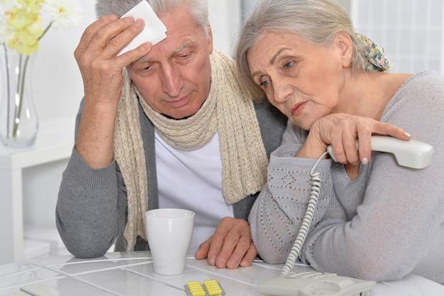 Kranker älterer mann und fürsorgliche frau telefonieren