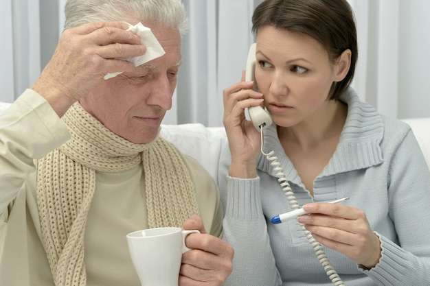 Kranker älterer mann und fürsorgliche tochter mit thermometerruf