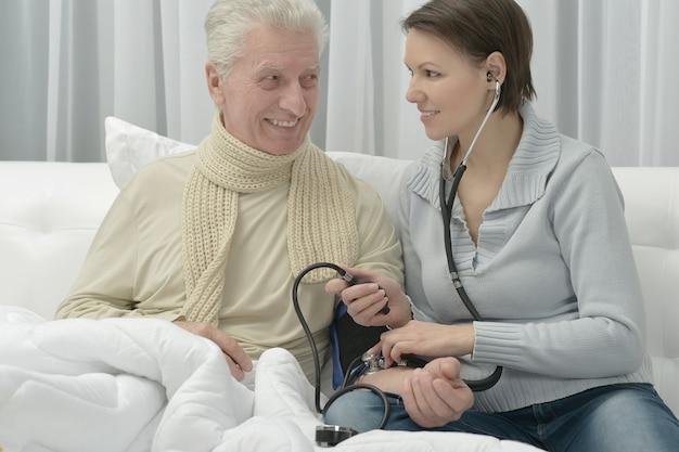 Kranker älterer mann und fürsorgliche tochter zu hause, die den blutdruck misst