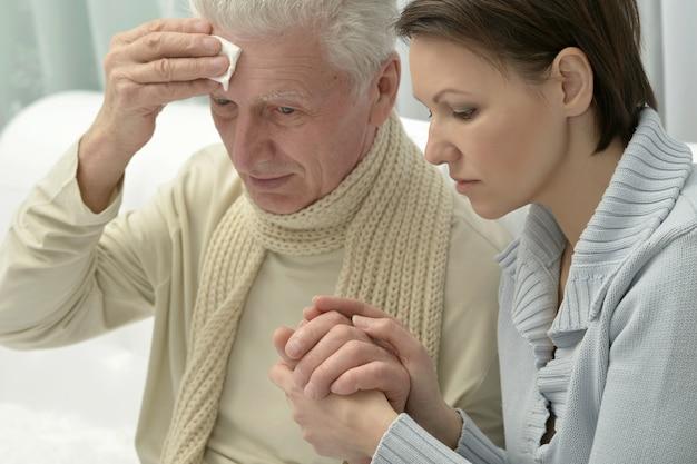 Kranker älterer mann und fürsorgliche tochter zu hause