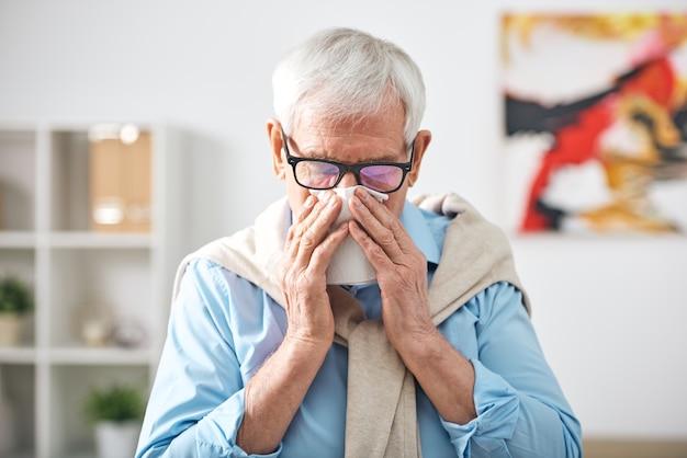 Kranker älterer rentner mit taschentuch an der nase, der zu hause bleibt, während er sich während der grippeepidemie unwohl fühlt