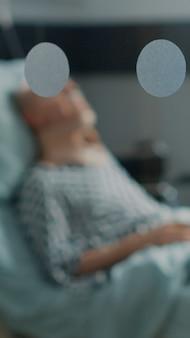 Kranker alter mann, der im krankenbett mit halskragen liegt