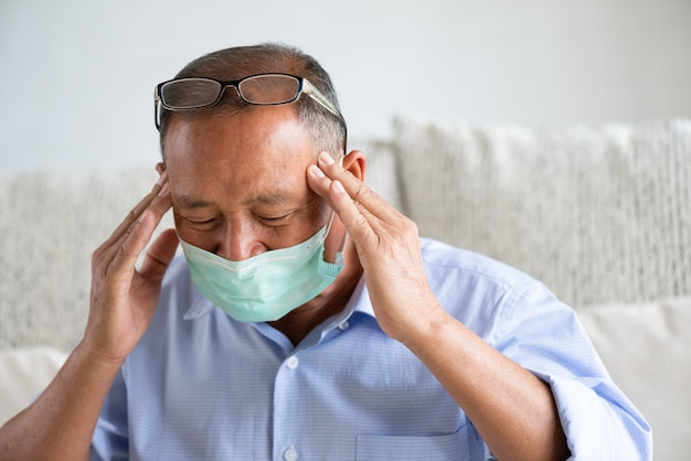 Kranker asiatischer alter mann, der schützende gesichtsmaske trägt und kopfschmerzen hat