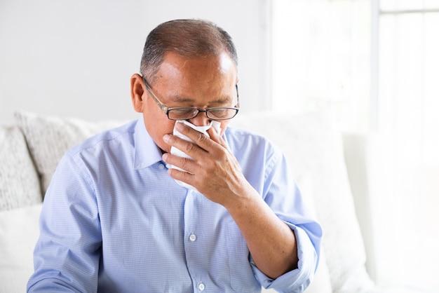 Kranker asiatischer alter mann mit seidenpapier schließen mund beim husten