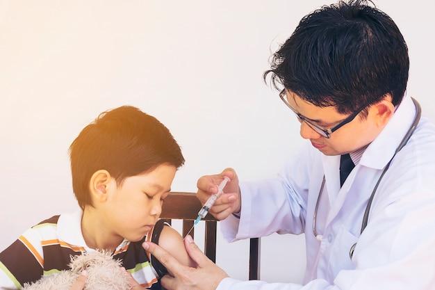 Kranker asiatischer junge, der vom männlichen doktor behandelt wird