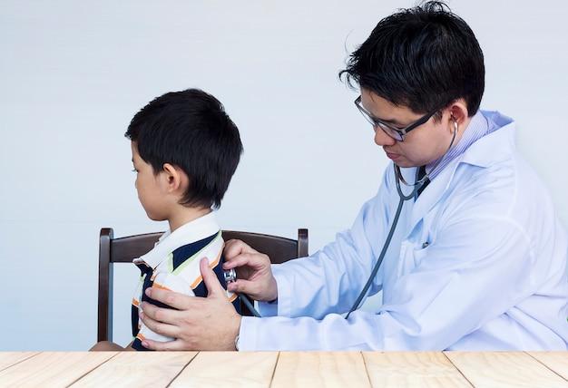 Kranker asiatischer junge, der vom männlichen doktor über weißem hintergrund überprüft wird