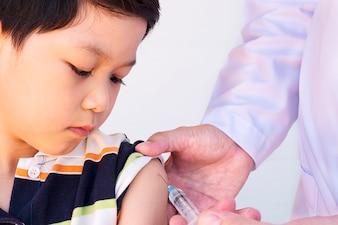 Kranker asiatischer Junge, der vom männlichen Doktor über weißem Hintergrund behandelt wird