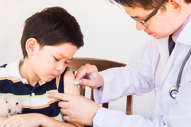 Kranker asiatischer junge, der von männlichem doktor über weißem hintergrund behandelt wird