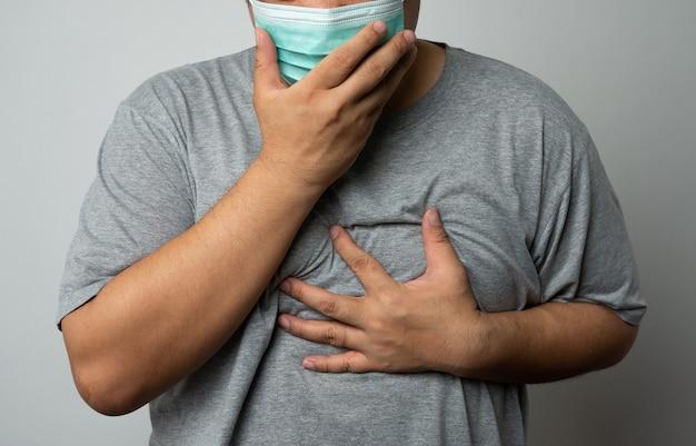 Kranker asiatischer mann, der eine medizinische gesichtsmaske trägt und hustet und seinen mund mit meiner hand bedeckt. konzept des schutzes pandemisches coronavirus und atemwegserkrankungen