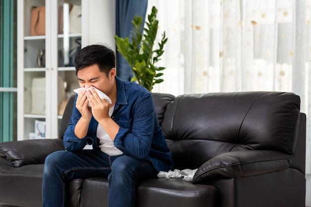 Kranker asiatischer mann, der seine laufende nase in papiertaschentuch putzt, sitzt zu hause auf dem sofa.